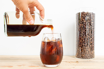 Person gießt Cold Brew in ein Glas